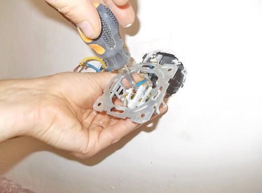 На фото показан процесс закрепления проводов к розетке
