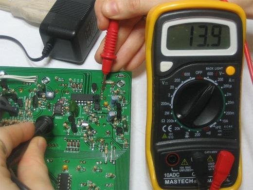 На фото проверка понижающего трансформатора мультиметром